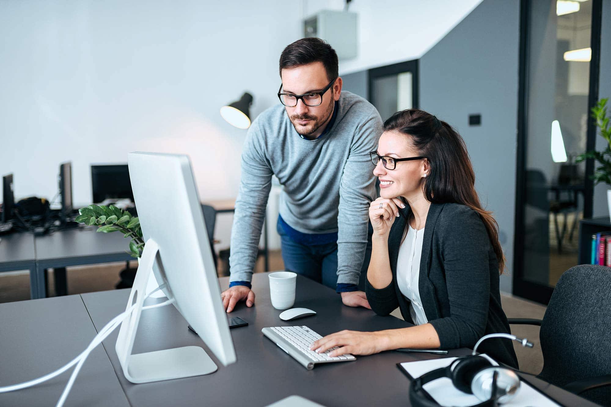 Man looking at computer monitor next to women